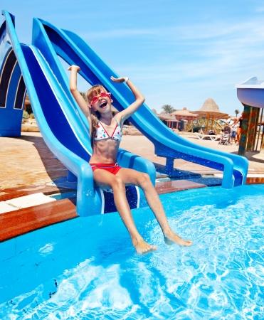 aqua park: Child on water slide at aquapark. Summer holiday.