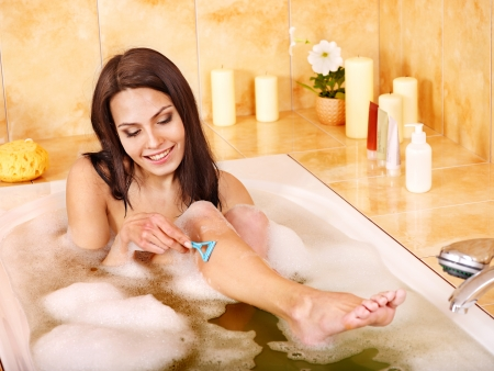 Young woman shaving her legs in  bath. photo