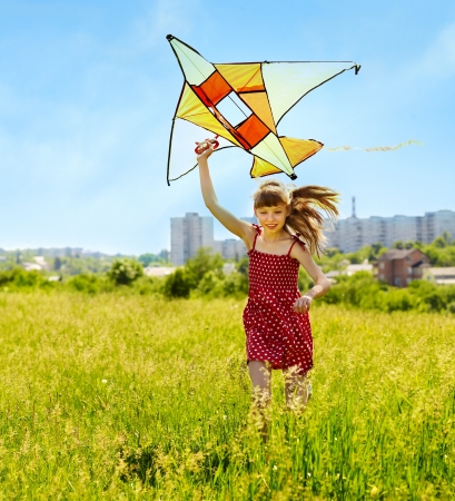 Child flying kite outdoor. little girl running across  green grass. photo