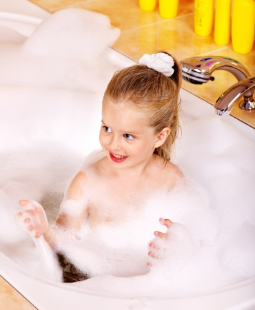 Happy child soaking in bubble bath . photo