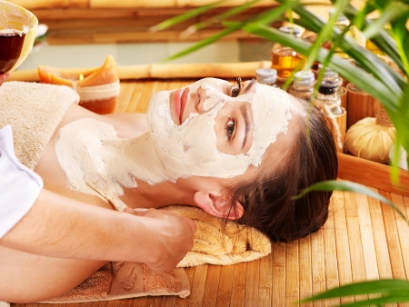 facial treatment: Woman having clay facial and body mask  apply by beautician.