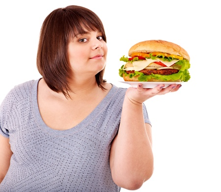 high calorie foods: Overweight woman eating hamburger. Isolated.