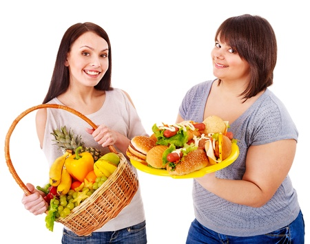 Women choosing between fruit and hamburger. Isolated. photo