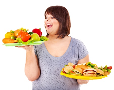 overweight: Woman choosing between fruit and hamburger. Isolated.