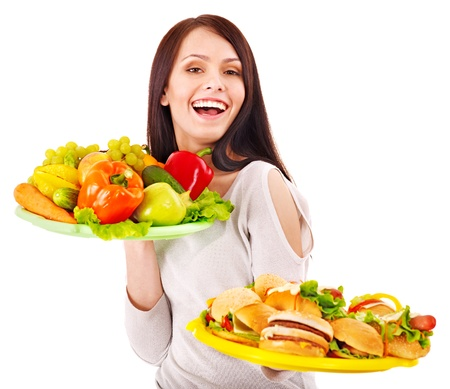Woman choosing between fruit and hamburger. Isolated. Stock Photo - 14104482
