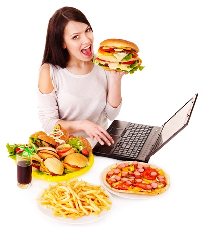 high calorie foods: Woman eating fast food at work. Isolated. Stock Photo