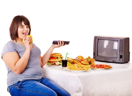fat person: Overweight woman eating fast food and watching TV. Isolated. Stock Photo