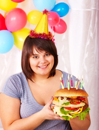 Overweight woman eating hamburger at birthday. Isolated. photo