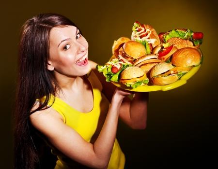 high calorie foods: Slim woman holding hamburger.