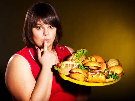 Overweight woman eating hamburger. Stock Photo - 14094795
