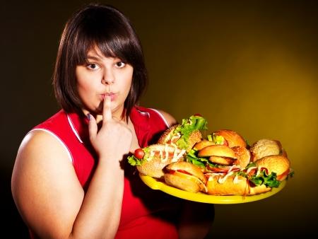 american food: Overweight woman eating hamburger.