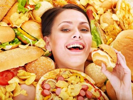 high calorie foods: Thin woman holding hamburger.