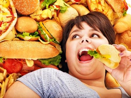 high calorie foods: Overweight woman holding hamburger.