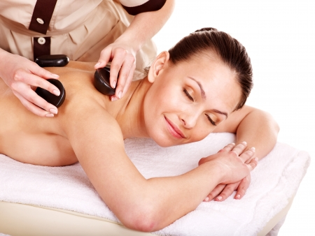 Woman getting stone therapy massage. Isolated. photo