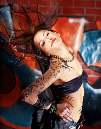 tatouage sexy: Femme avec l'art corporel aganist mur de briques graffiti. Banque d'images