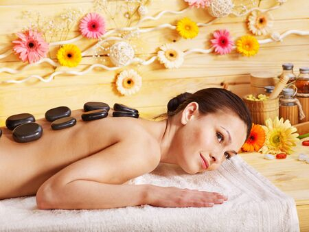 Woman getting stone therapy massage in wooden spa. photo