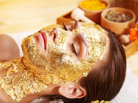 Woman getting  gold facial mask. Reklamní fotografie - 14104849