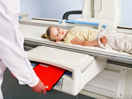 Child patient  in x-ray room looking at doctor. Stock Photo - 14092404