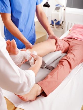 Doctor en vendar los pies del paciente en el hospital. photo