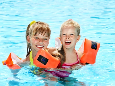 Children with armbands in swimming pool. photo