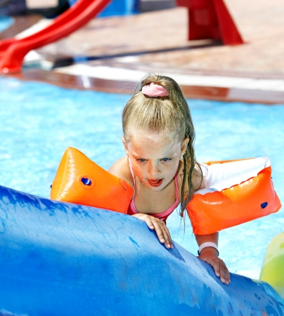 Child with armbands playing at water. Summer outdoor. photo