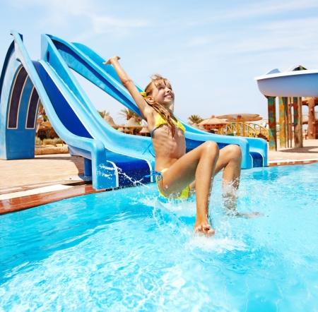 Niño en diapositiva de agua en aquapark. Vacaciones de verano.