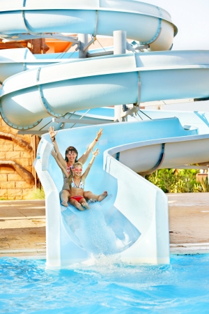 Child with mother on water slide at aquapark. photo
