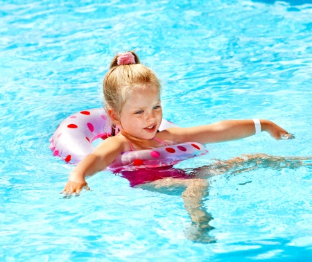 Little girl sitting on inflatable ring in swimming pool. photo