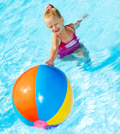 Little girl  playing beach ball in swimming pool. photo