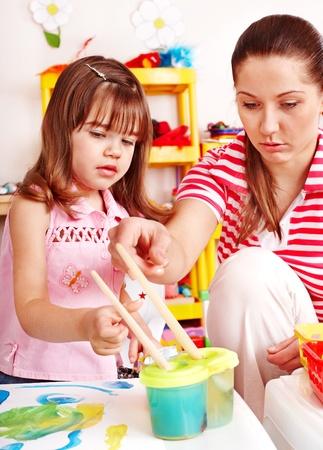 nurser: Child with teacher draw paints in play room. Preschool.