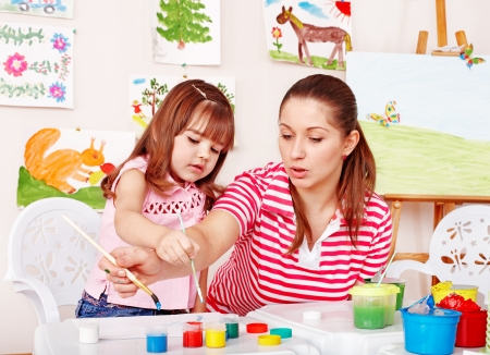 daycare: Child with teacher draw paints in play room. Preschool.