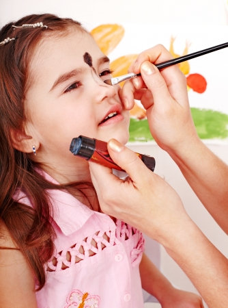 Child preschooler with face painting. Make up. photo
