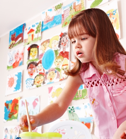 CHILD CARE: Little girl paint picture in preschool. Child care.