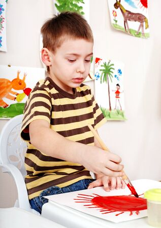 Child with picture and brush in play room. Preschool. Imagens