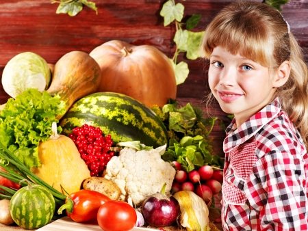Little girl with vegetable on kitchen.n. photo