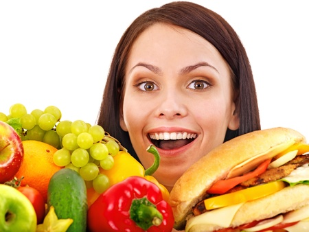 Woman choosing between fruit and hamburger. Isolated. Stock Photo - 14529065