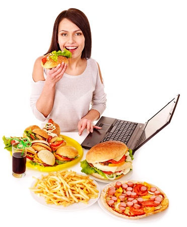 Woman eating fast food at work. Isolated. Stock Photo - 14528959