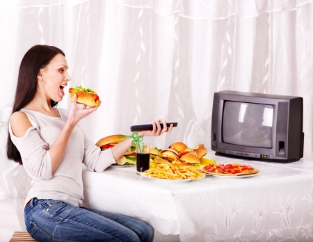 Woman eating fast food and watching TV. Isolated. photo