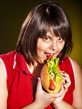 Overweight woman eating hamburger. photo