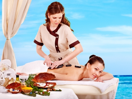 Young woman getting spa lastone therapy outdoor. photo