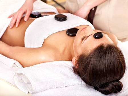 Woman getting stone therapy massage in spa. photo