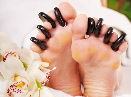 massage jambe: Femme recevant massage aux pierres chaudes sur les pieds.