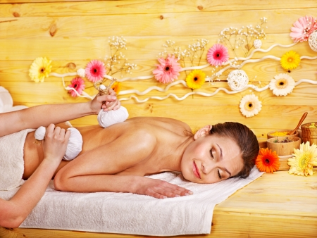 Woman getting herbal ball massage  in spa. photo