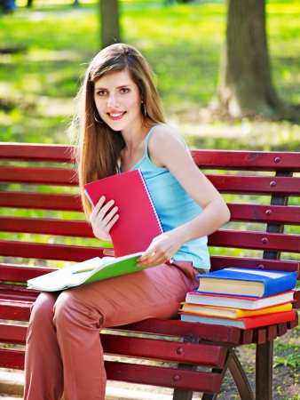 Student with book on bench outdoor. photo