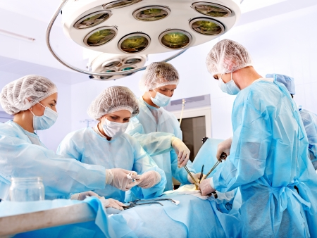 paciente: Equipo de cirujanos en el trabajo en sala de operaciones.