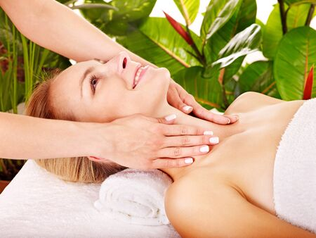 Woman getting facial massage in tropical beauty spa. photo