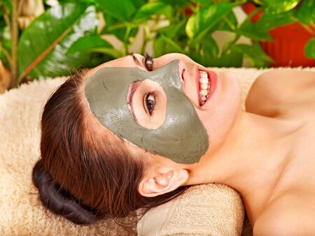 Woman getting facial mask in tropical beauty spa. photo