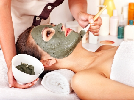 facial spa: Woman with clay facial mask in beauty spa. Stock Photo