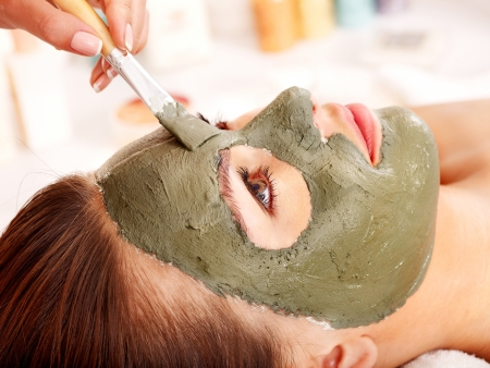 mud woman: Woman with clay facial mask in beauty spa. Stock Photo