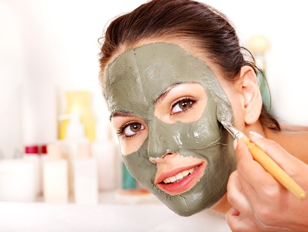 Woman with clay facial mask in beauty spa. Imagens